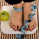 Woman foot on measuring scale with tape and apple.